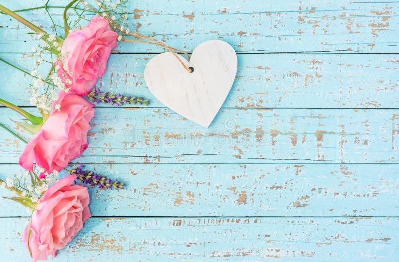 Roze rozen met hart op pastelkleur blauw hout stock foto