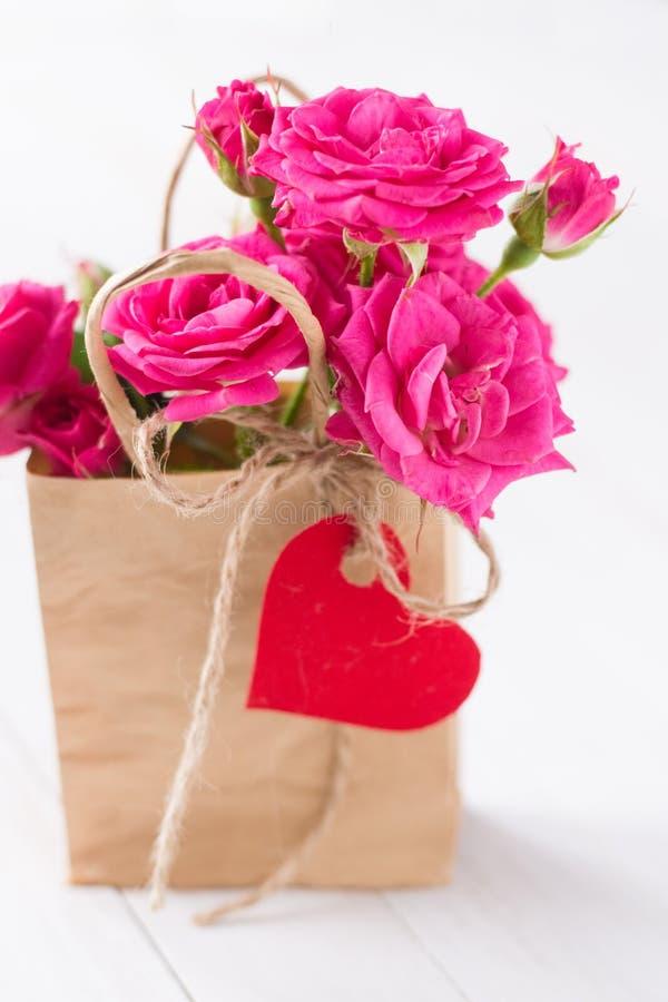 Roze rozen in papierzak met rood hart stock afbeeldingen