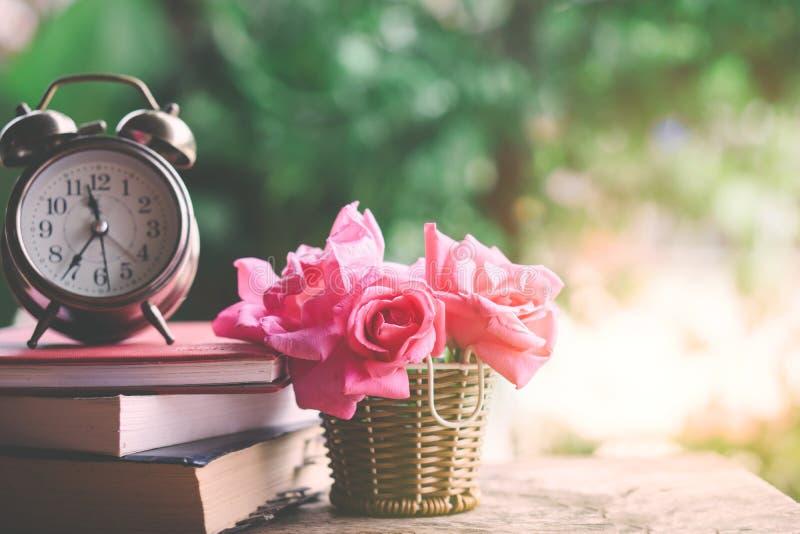 Roze rozenboeket, klok en boek op houten lijst stock afbeelding