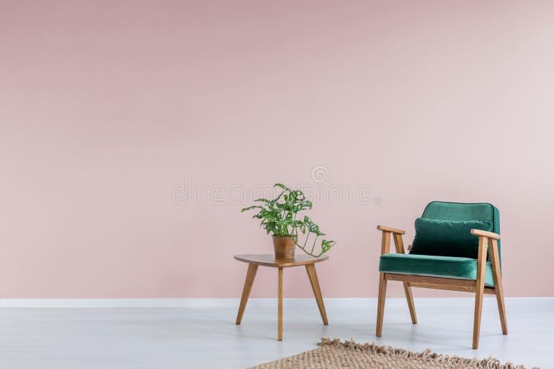 Roze ruimte met groene leunstoel royalty-vrije stock fotografie