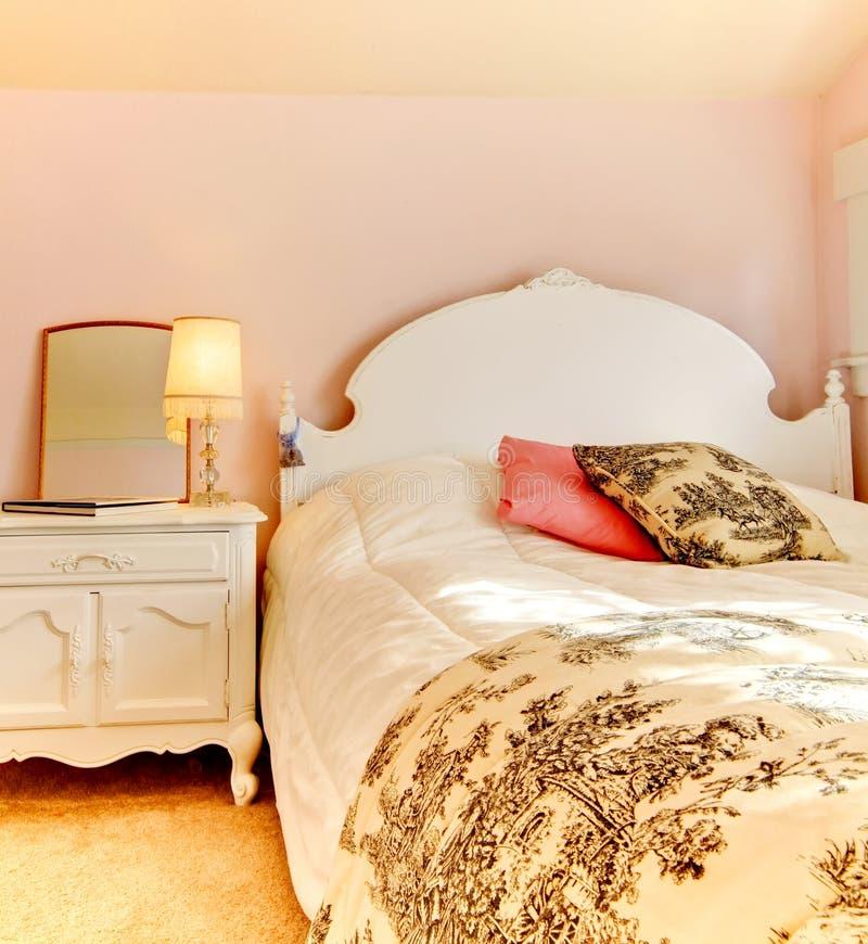 Roze slaapkamer met wit bed en nightstand royalty-vrije stock fotografie