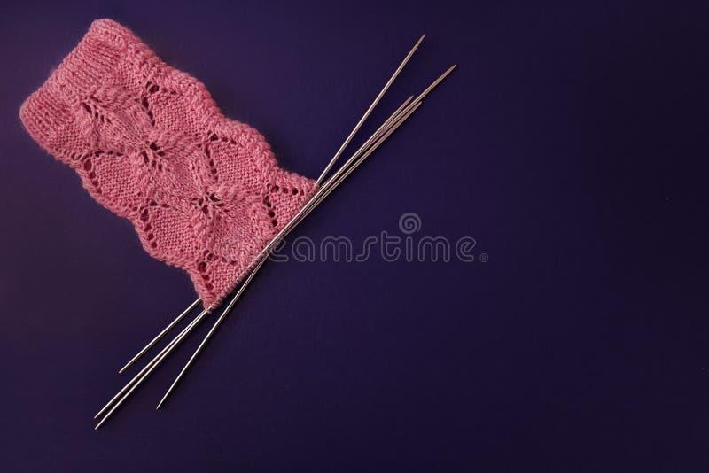 Roze sokken die van wol worden gemaakt, die met een openwork patroon op vier breinaalden op donkere purpere achtergrond wordt geb stock foto