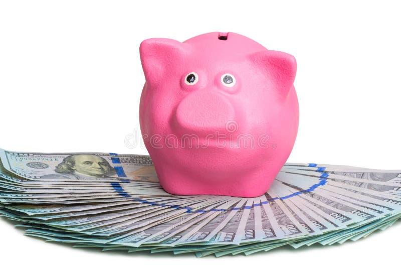 roze spaarvarken die op een ventilator van een stapel van Amerikaanse dollars op een witte achtergrond bevinden zich stock afbeelding
