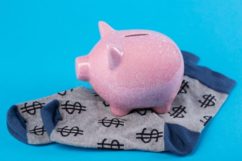 Roze spaarvarken die op grijze sokken met dollarsymbool, financiën en accumulatieconcept bevinden zich stock fotografie