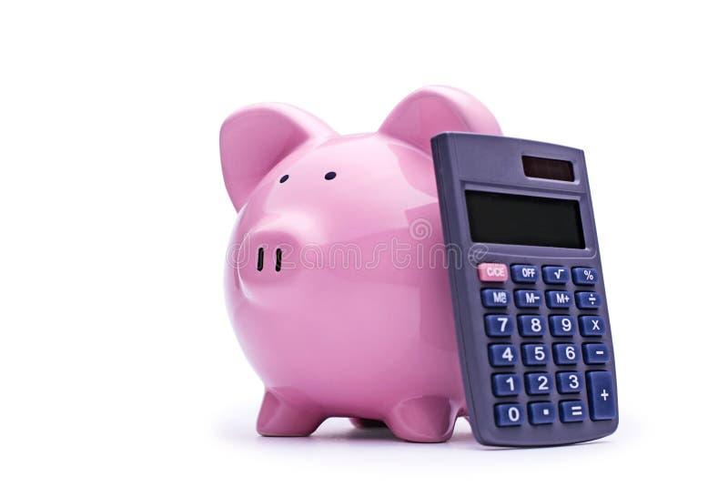 Roze spaarvarken met een calculator stock fotografie