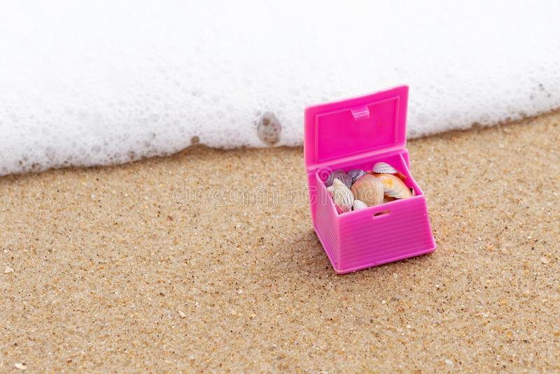 Roze stuk speelgoed borst met shells, op een zandig strand, met overzeese golf, reis en avonturenconcept, macro stock foto's