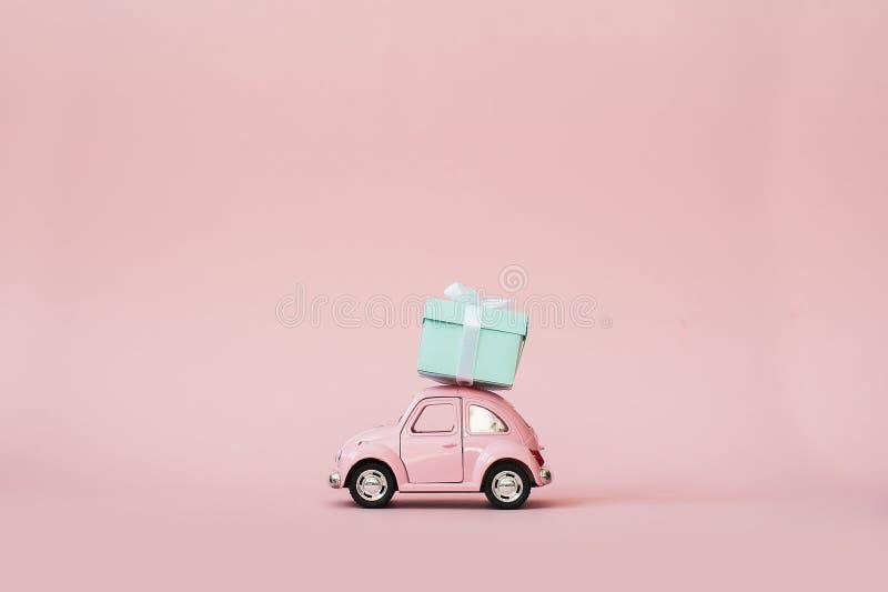 Roze stuk speelgoed retro modelauto die giftdoos leveren voor de dag van Valentine ` s op roze achtergrond Volkswagen Beetle op r stock afbeeldingen
