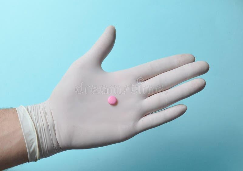 Roze tablet op doktershand met witte latexhandschoenen op een blauwe achtergrond MEDISCH concept royalty-vrije stock foto's