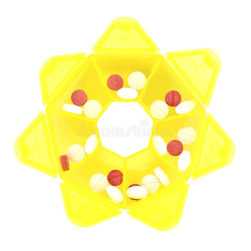 Roze tabletten in een geel pillendoosje voor drugs royalty-vrije stock foto