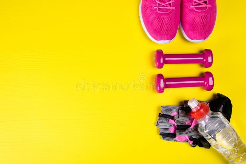 Roze tennisschoenen en toebehoren voor geschiktheid, en een fles water, op een gele achtergrond, met een plaats voor het schrijve stock afbeelding