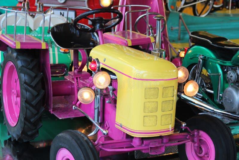 Roze tractor op een kinderencarrousel stock fotografie