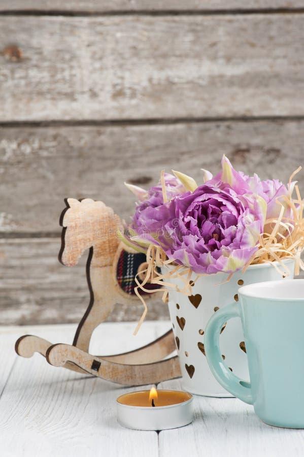 Roze tulpen, blauwe kop, aangestoken kaars en hobbelpaard stock afbeelding
