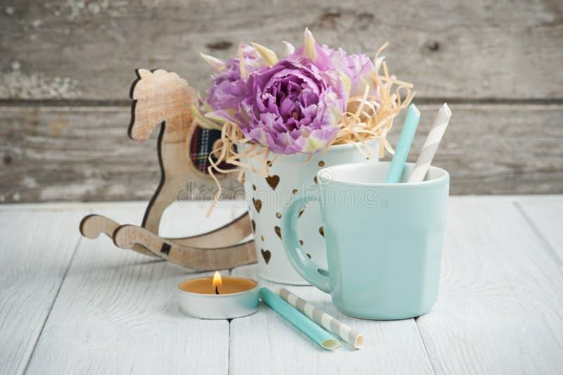 Roze tulpen, blauwe kop, stro, aangestoken kaars en hobbelpaard stock fotografie
