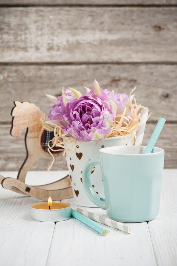 Roze tulpen, blauwe kop, stro, aangestoken kaars en hobbelpaard stock afbeelding