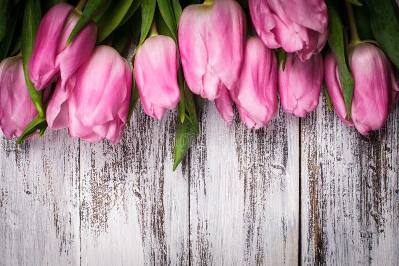 Roze tulpen over houten lijst stock afbeeldingen