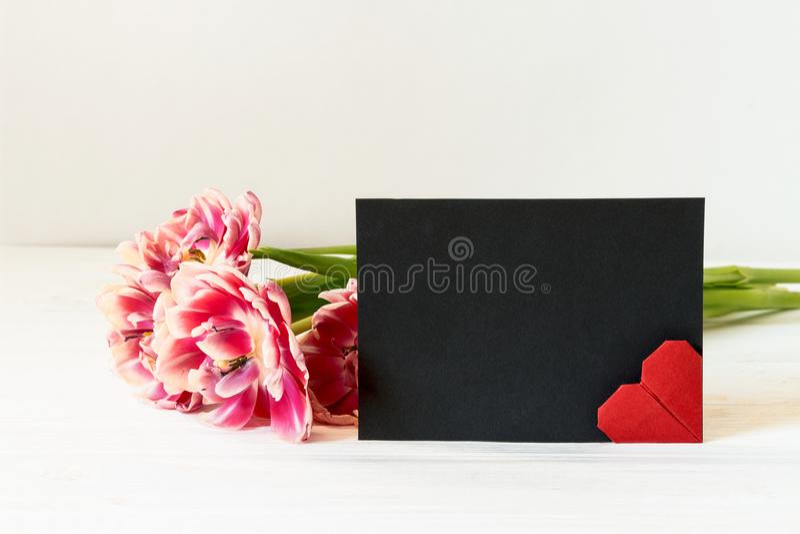 Roze tulpen, rood origamihart en horizontale zwarte document lege kaart met exemplaarruimte royalty-vrije stock afbeelding
