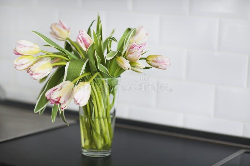 Roze tulpenboeket in glasvaas op de keuken stock afbeelding