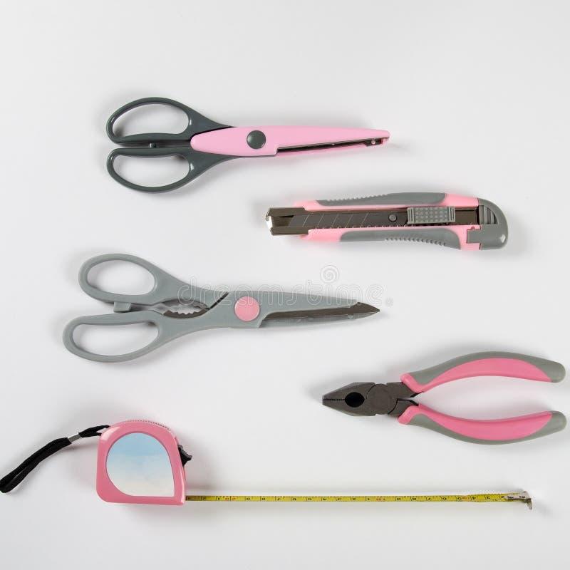 Roze vrouwelijke handige hulpmiddelen op een witte achtergrond royalty-vrije stock afbeeldingen