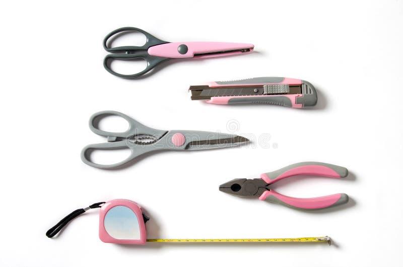 Roze vrouwelijke handige hulpmiddelen op een witte achtergrond stock afbeeldingen