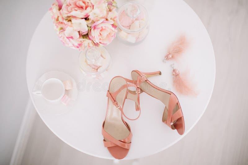 Roze vrouwenschoenen, een boeket van de lentebloemen en heemst op witte achtergrond Ochtend van de Bruid Vlak leg stock afbeeldingen