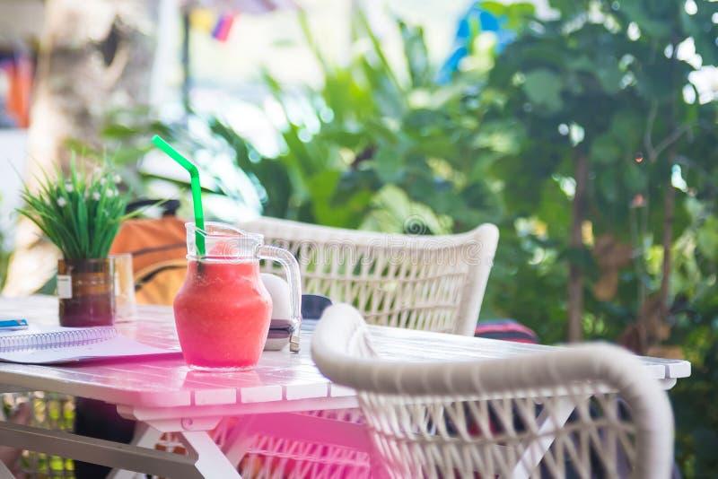 Roze watermeloen smoothie van tropische vruchten op de witte houten lijst in kruik met stro bij zonnige dag Ontspan in de tuinkof royalty-vrije stock foto