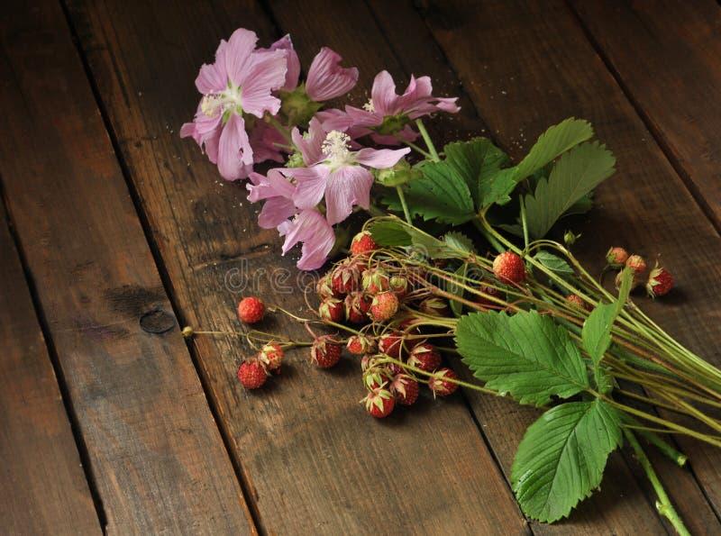 Roze wildflowers en wilde aardbei op een oude houten achtergrond Stilleven 1 royalty-vrije stock afbeeldingen