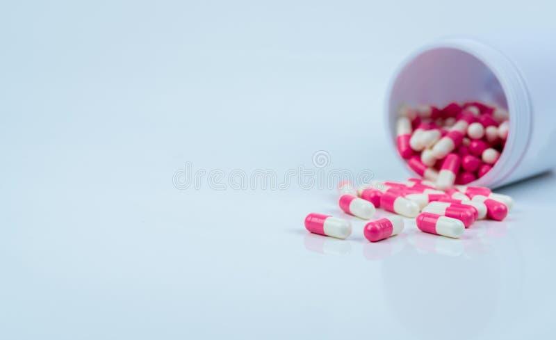 Roze-witte capsulepillen die uit drugfles worden uitgespreid Antipsychotic drug Capsulegeneeskunde voor behandelingsdepressie Ant royalty-vrije stock afbeelding