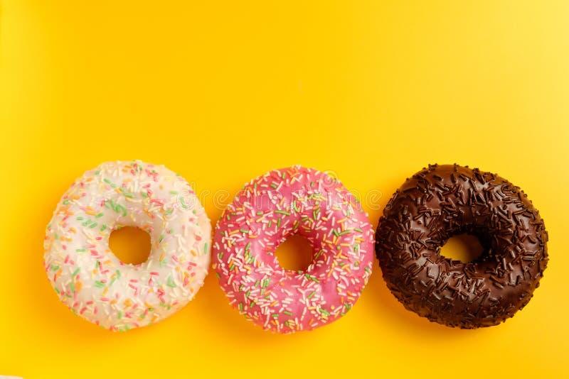 Roze witte en zwarte chocolade donuts op de gele ruimte van het achtergrond hoogste meningsexemplaar royalty-vrije stock afbeeldingen