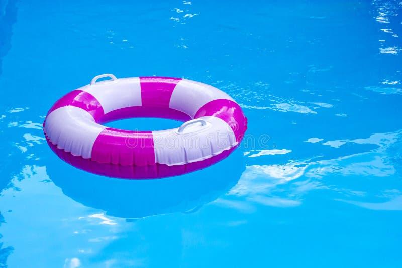 Roze-witte zwembadring, vlotter in het verfrissen van blauw water Zonnige dag bij toevlucht royalty-vrije stock afbeelding