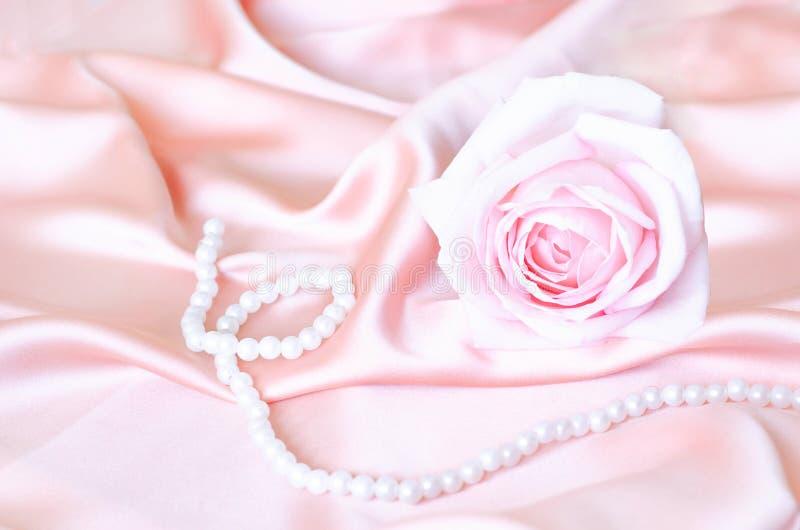 Roze zacht nam met een parelhalsband toe op satijnstof royalty-vrije stock foto's