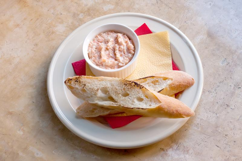Roze zalmrillette Pastei van gerookte vissen in witte plaat, geroosterd baguettebrood zachte nadrukclose-up stock foto