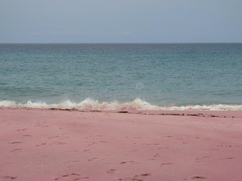 Roze zandig strand met voetafdrukken in het zand en de bespattende golven, achtergrond royalty-vrije stock fotografie
