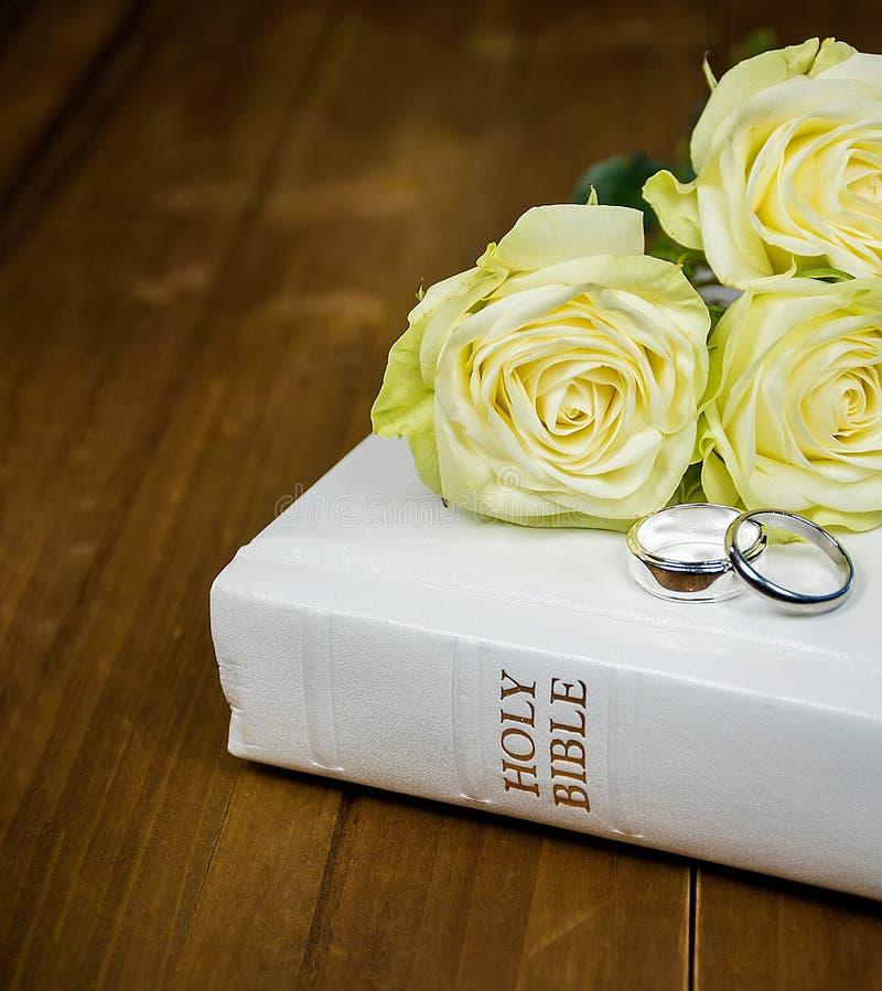 Rozen en ringen op witte Bijbel royalty-vrije stock afbeelding