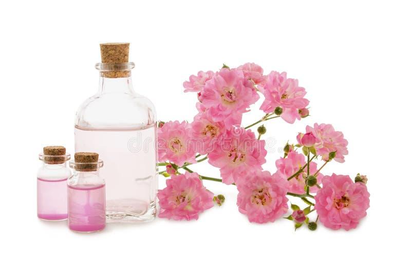 Rozenwater of olie in glasflessen en roze die bloemen op wit worden geïsoleerd stock fotografie