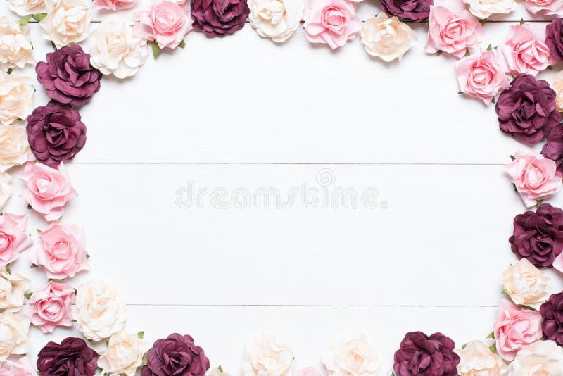 Rozerood en wit rozenkader op witte houten achtergrond met e royalty-vrije stock afbeelding