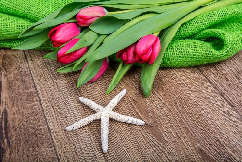 Download Rozgwiazda I Tulipany Na Drewnianym Stole Zdjęcie Stock - Obraz złożonej z wakacje, pomysł: 106910372