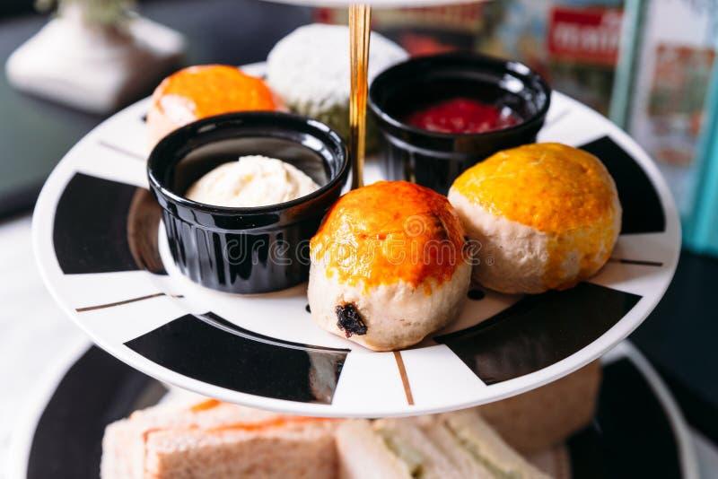 Rozijnenscone en Duidelijk Scone op zwart-witte kleurenplaat Gediend met jam en boter royalty-vrije stock foto