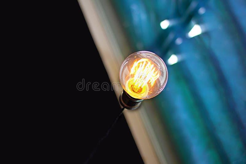 Rozjarzona żółta żarówka z jaskrawym helix incide na przekątny linii między czerni pustą ścianą i błękitnymi lampasami z flecks e fotografia stock