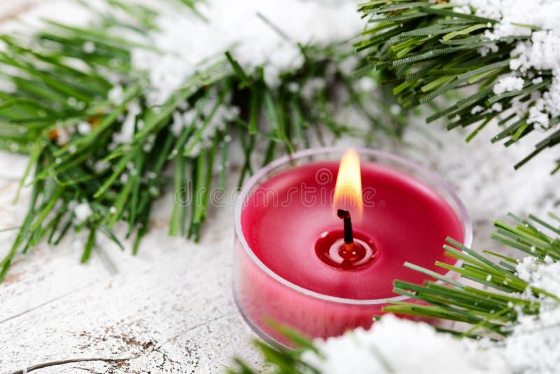 Rozjarzona świeczka dla Bożenarodzeniowego wakacje z wiecznozielonym wewnątrz i śnieżnym obrazy stock