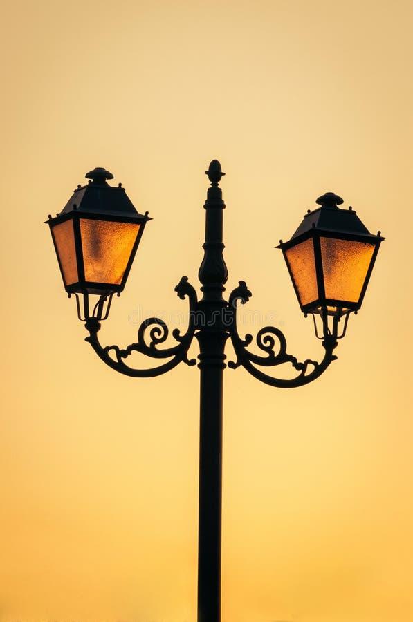 Rozjarzone latarnie uliczne na zmierzchu niebie fotografia stock