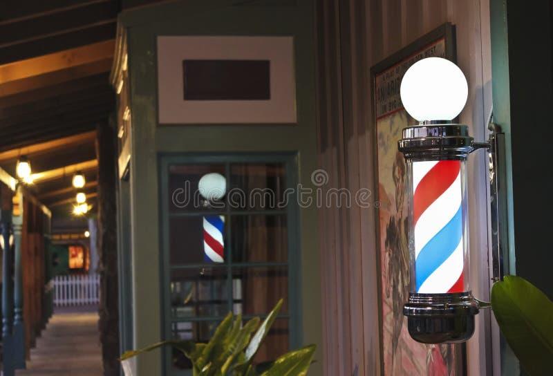 Rozjarzony fryzjera męskiego słup na Sklepowym ganeczku obraz stock