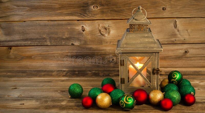 Rozjarzony lampion z boże narodzenie ornamentami na Nieociosanym drewnie zdjęcia stock