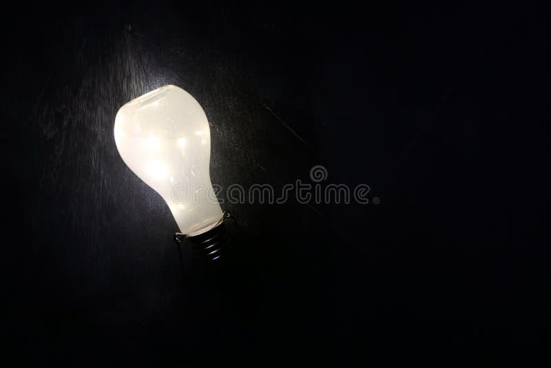 Rozjarzony lightbulb na czarnym tle fotografia stock