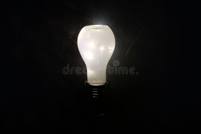 Rozjarzony lightbulb na czarnym tle obrazy stock