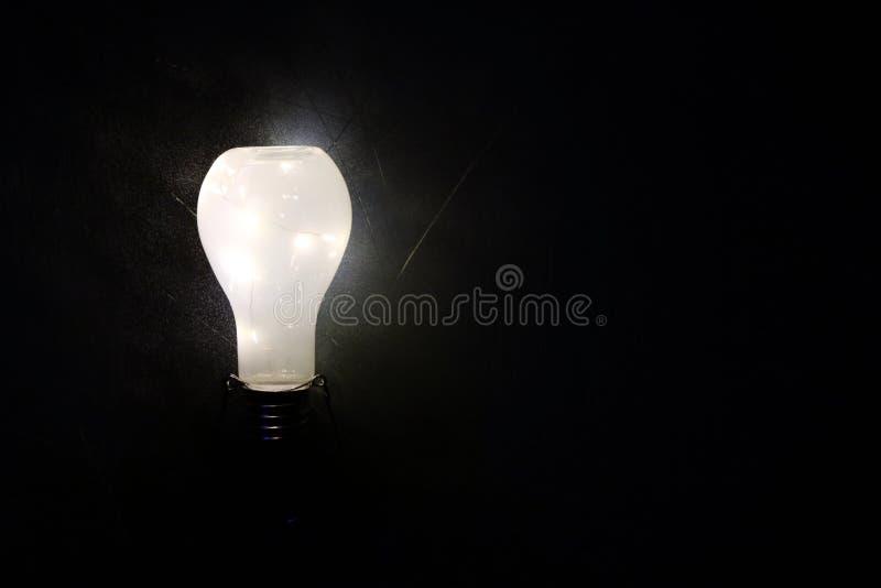 Rozjarzony lightbulb na czarnym tle obraz stock