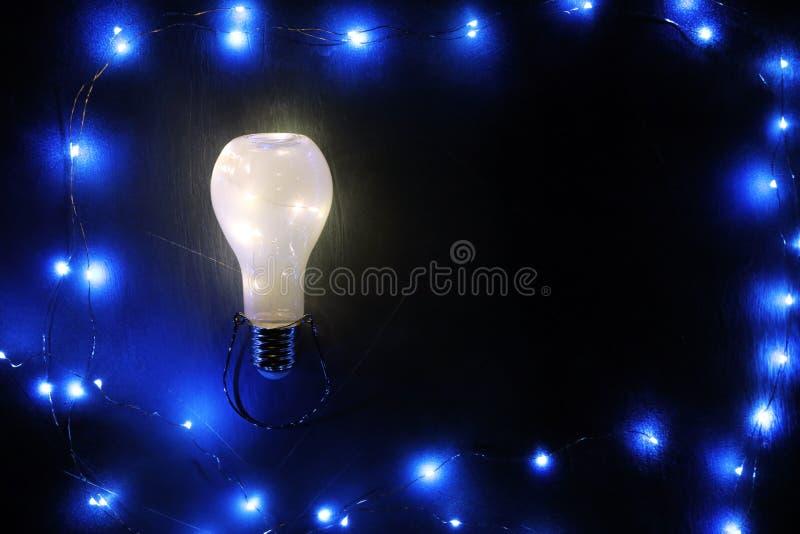 Rozjarzony lightbulb na czarnym tle royalty ilustracja