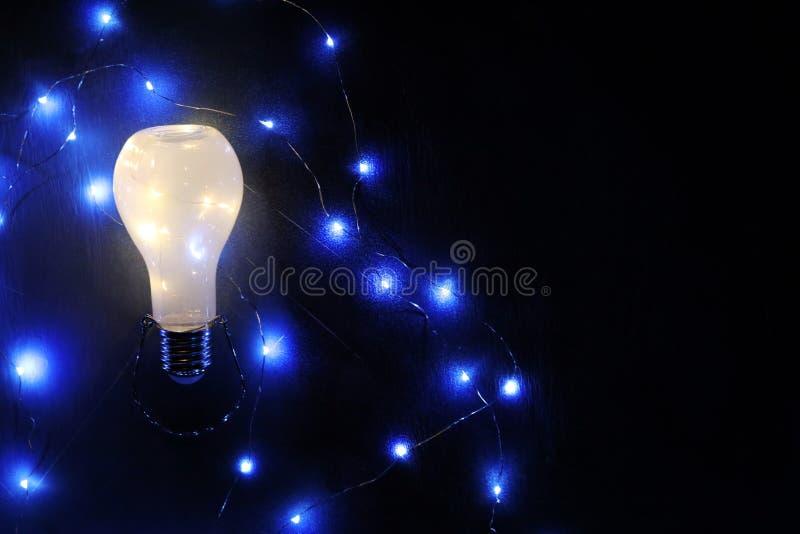 Rozjarzony lightbulb na czarnym tle ilustracji
