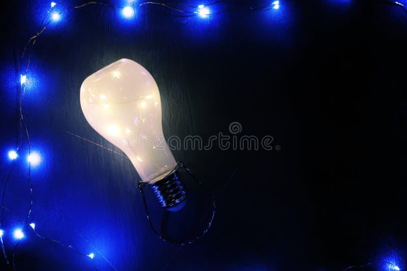 Rozjarzony lightbulb na czarnym tle ilustracja wektor