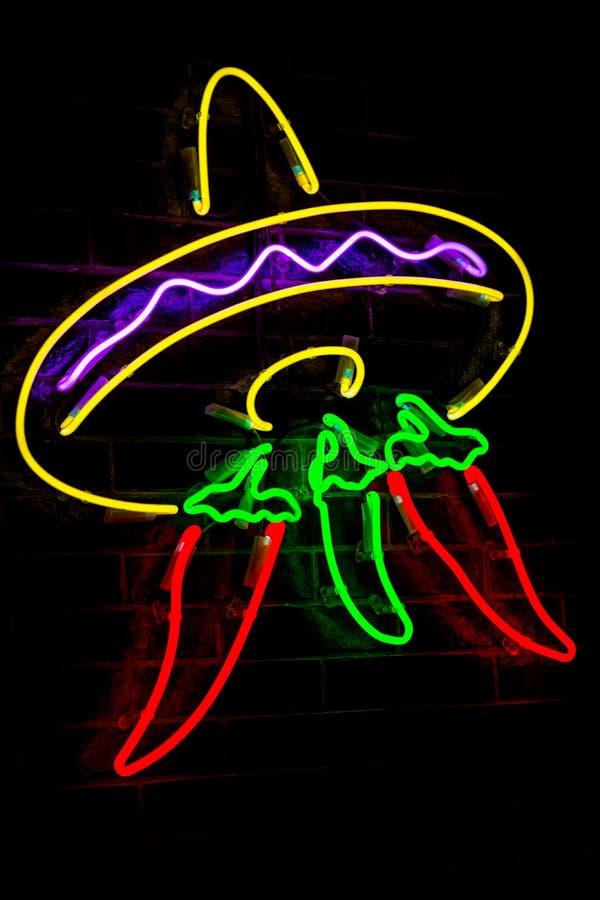 Rozjarzony Neonowy stylizowany meksykański sombrero, czerwoni pieprze i zamazujący światła na czarnym ściany z cegieł tle obraz stock