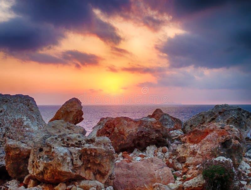 rozjarzony złoty zmierzch otaczający iluminować chmurami nad spokojnym morzem śródziemnomorskim z przedpolem nabrzeżne skały barw obraz royalty free